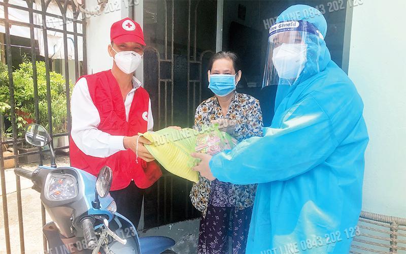 Tình nguyện viên Hội Chữ thập đỏ TP Hồ Chí Minh tặng quà cho F0 tại quận Bình Tân.